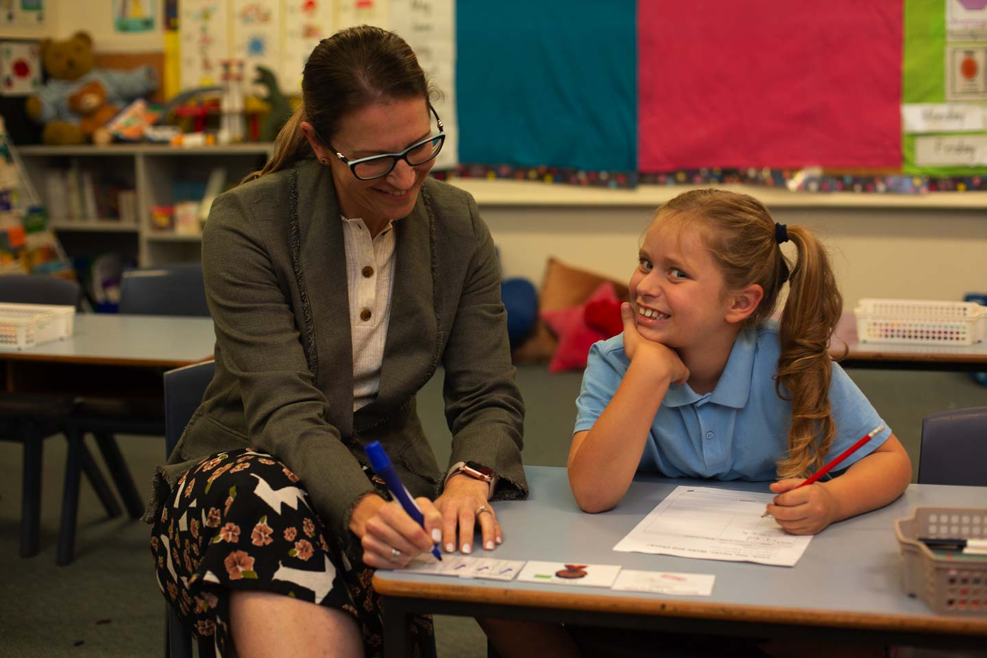 Teacher with child in classroom for positive teaching and behaviour support