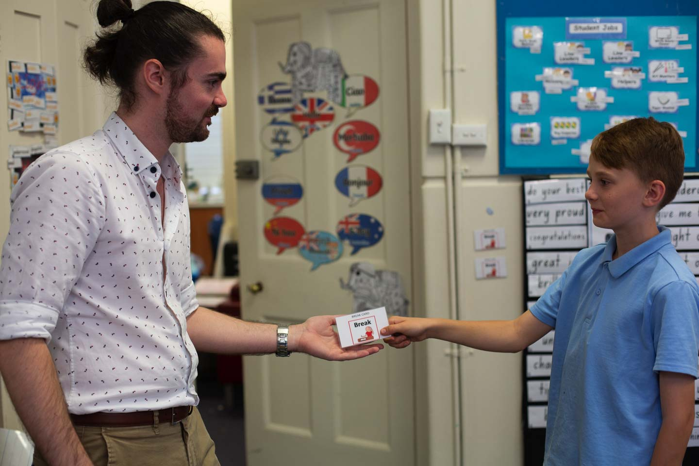 Classroom teacher presenting break out card to young student